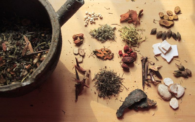 High Angle View Of Herbs And Spices By Container On Table