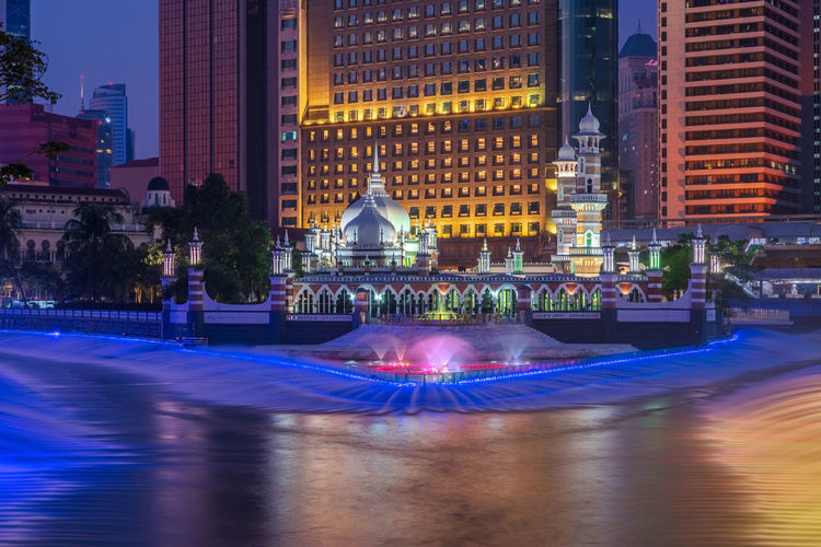 Illuminated fountain in city at night