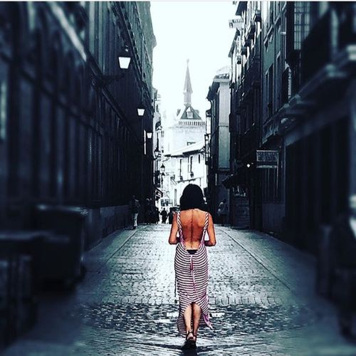 Rear view of woman walking on wet alley amidst buildings in city
