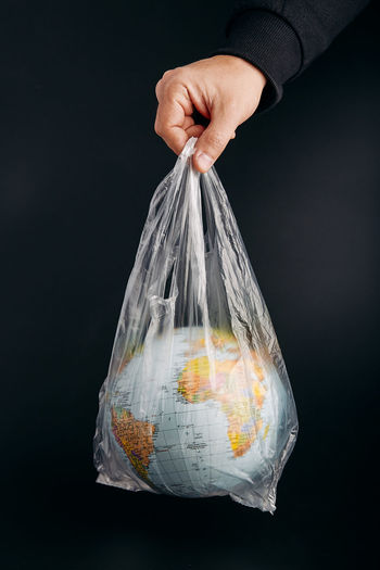 Cropped man holding globe in plastic bag against black background