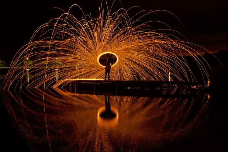 Man spinning wire wool while standing on pier over lake at night