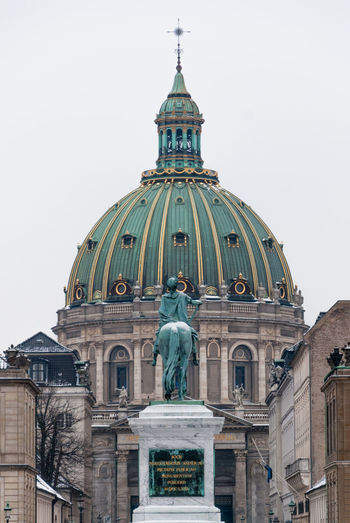 Low angle view of statue and frederik church against sky