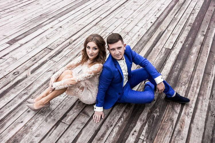 High angle portrait of bride and bridegroom sitting on wooden footpath