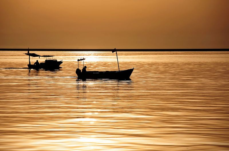 Fishing and fishingboat Water Sunset Nautical Vessel Sky Transportation Beauty In Nature Mode Of Transportation Sea Waterfront Silhouette Nature Scenics - Nature Reflection Orange Color Idyllic Occupation Men Horizon Over Water Tranquility Outdoors