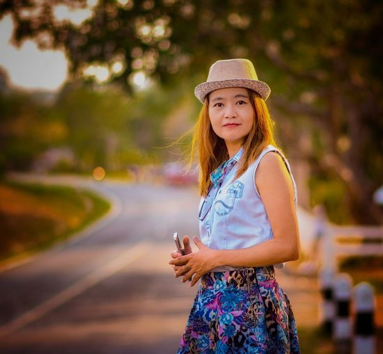Portrait of woman wearing hat while standing on road