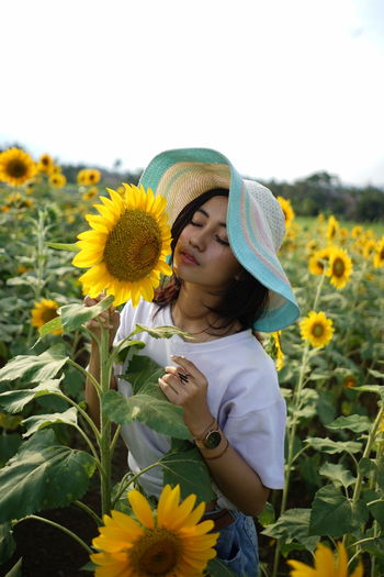 Low angle view of girl on sunflower field
