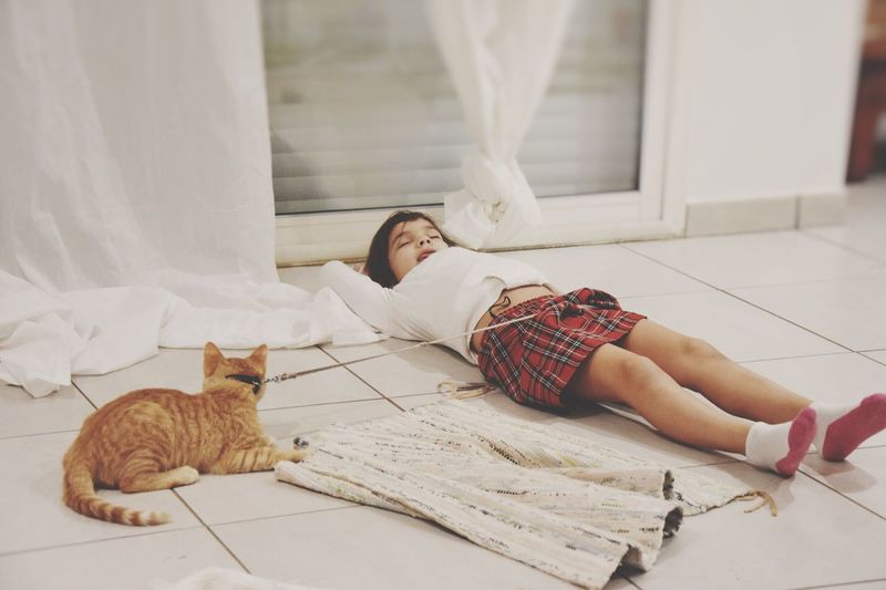 Girl sleeping with cat on tiled floor at home