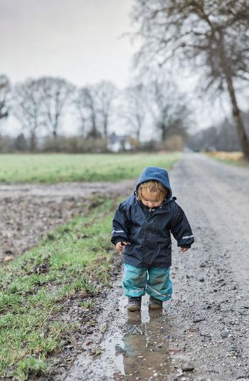 Full Length Of Cute Girl Walking On Muddy Road