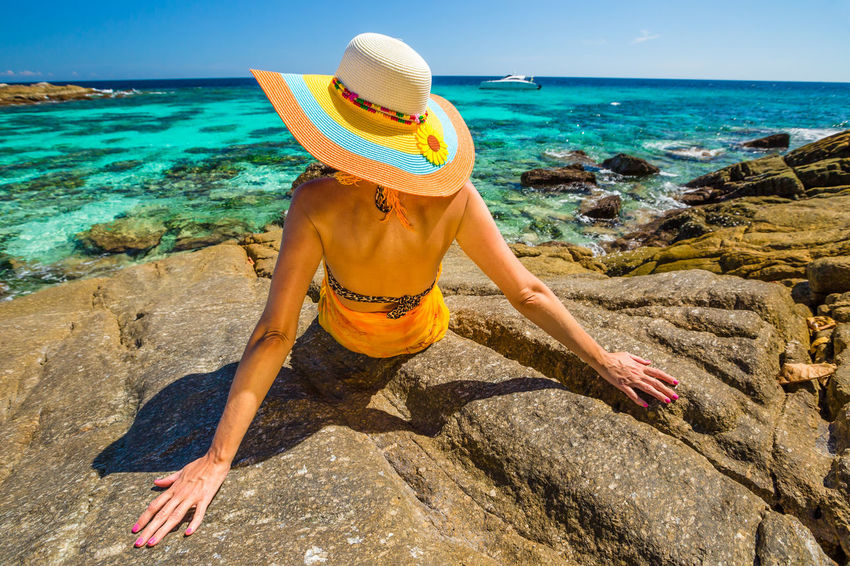 Back of happy and fashionable tourist woman with colorful sarong in turquoise water of Maya Bay famous lagoon of The Beach movie, Phi Phi Leh, Andaman Sea in Thailand Fashionable and happy tourist with sarong and pink wide-brimmed hat making a selfie on tropical famous beach of Nai Harn Beach, Rawai, Phuket, Thailand. Happy tourist enjoys panorama from Sail Rock View Point of kor 8 of Similan Islands National Park, Phang Nga, Thailand, one of the tourist attraction of the Andaman Sea. Happy woman with bikini and shorts, jumping in the air on Ya Nui Beach, a little cove divided by a rocky cape, Phuket, Thailand, Asia. Happy Koh Rok Islands Nui Beach Phang Nga Bay Phuket Thailand Tanning ☀ Thailand Vacations Woman Adult Adults Only Beach Beauty In Nature Day Full Length Girl Horizon Over Water Koh Rok Leisure Activity Lifestyles Nature One Person Outdoors People Phang Nga Rawai Real People Rear View Rock - Object Scenics Sea Seascape Sky Standing Surin Islands Travel Destinations Vacations Water Women Young Adult
