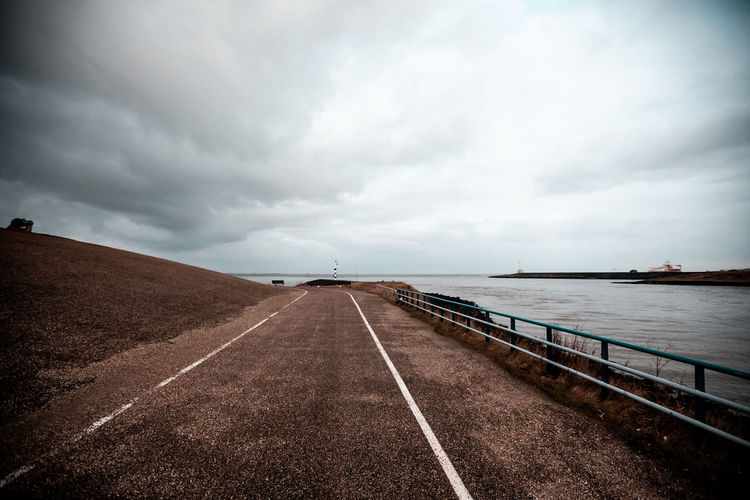 Empty road by sea against sky