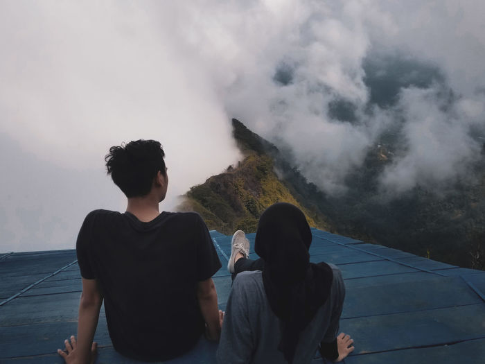 People standing on mountain against sky