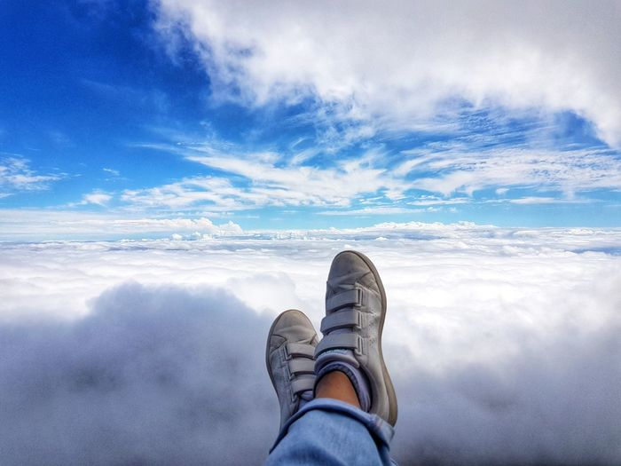Low section of man against cloudscape