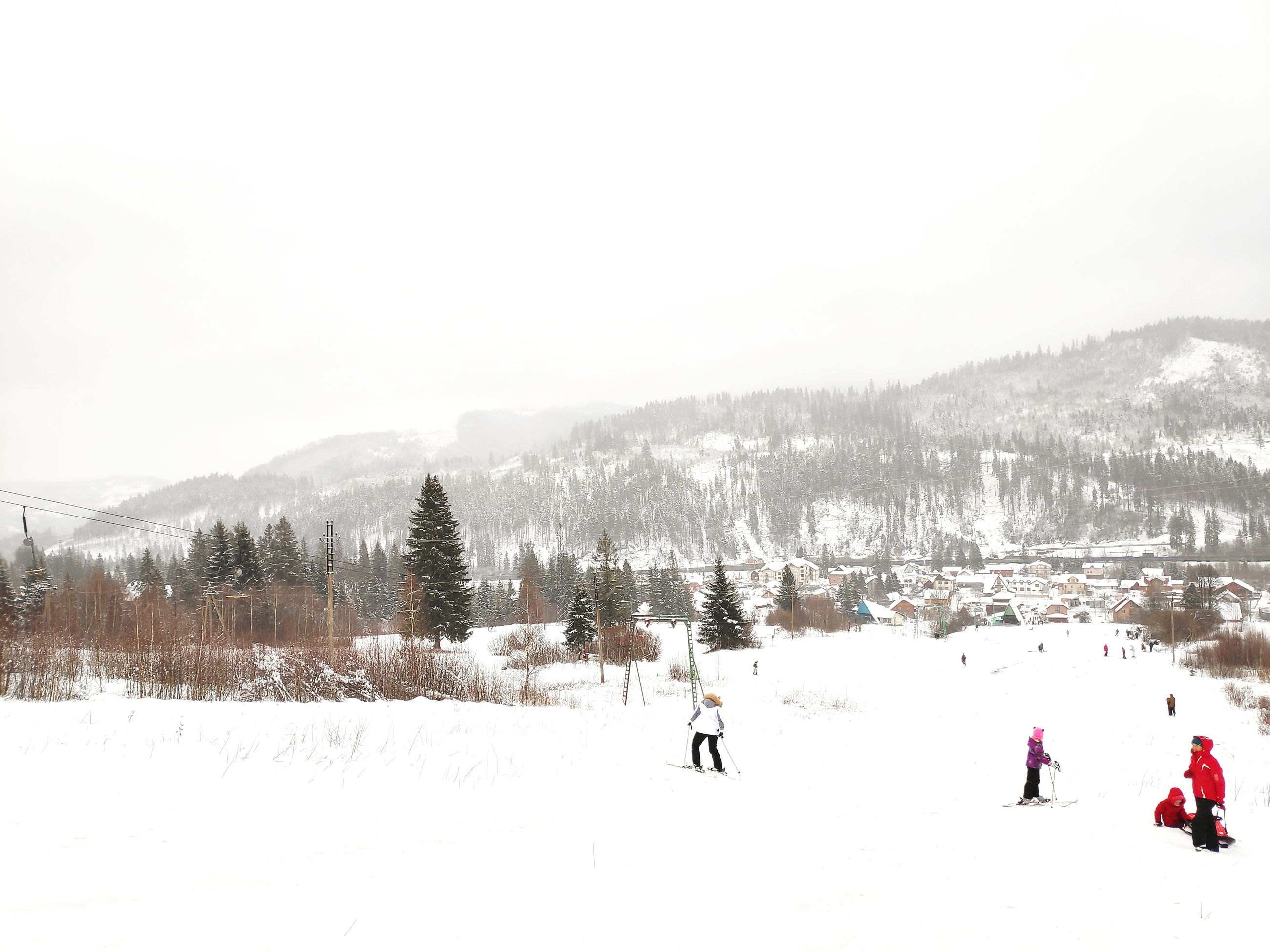 snow, winter, cold temperature, sky, mountain, beauty in nature, nature, scenics - nature, real people, tree, group of people, field, land, winter sport, day, copy space, sport, covering, skiing, mountain range, outdoors, snowcapped mountain, warm clothing