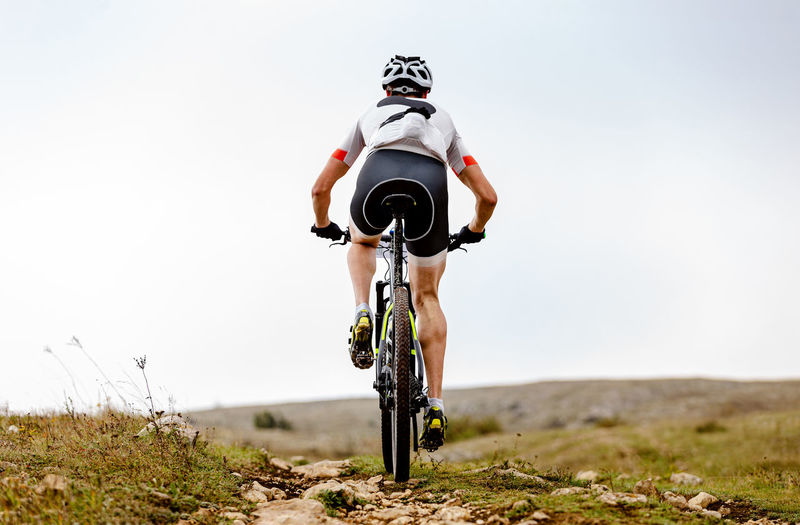Lone male cyclist riding on mountain road in background sky