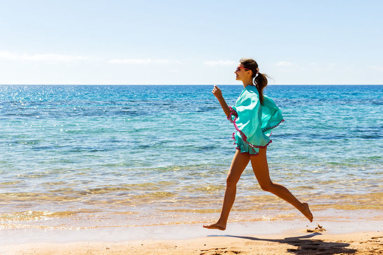 Full length side view of young woman running on shore at beach during summer