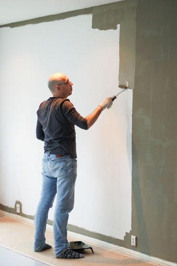 One Person Standing Full Length Indoors  Casual Clothing Lifestyles Occupation Home Interior Home Improvement Painting Wall Jeans Maintenance Renovation Painter Handyman Paint Roller Do It Yourself Man At Work Standing Tall Bald Head Man Working Man Painting Wall Living Room Living Room View Bald Man