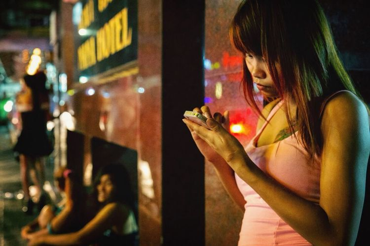 Everyday Lives Damien Guyon - Endymion Photographies - True Smiles under the Red Light - Website : http://endymion-photo.com Girls Thailand Waiting Bangkok Bangkok Thailand. Nightlife Phone Nightphotography Streetphotography