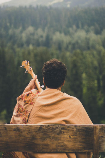 Rear view of man playing guitar sitting on bench