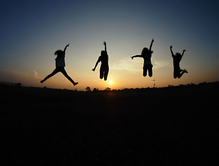 Silhouette people jumping on field against sky during sunset