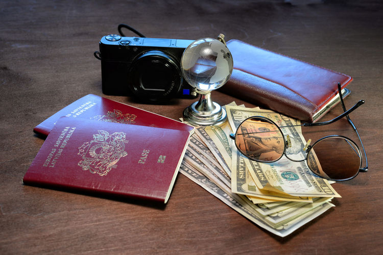 Sunglasses, a glass globe, passports, camera, notebook and money on a dark wooden background. Tourism concept. Dollar Money Cash Savings Banking Finance Bill Currency Wealth Background Banknote Bussiness Profit Green Close-up USD Exchange Loan  Paper Sign Payment Pay Stack Number Textured  Abstract Earnings Symbol Capital Assets Sunglasses Camera Photography Passport Passports Glass Glass - Material Globe Note Notebook Wood - Material Travel Tourism Concept Table Paper Currency Glasses Indoors  Business No People Still Life High Angle View Book Photography Themes Publication Camera - Photographic Equipment Technology Eyeglasses  Economy