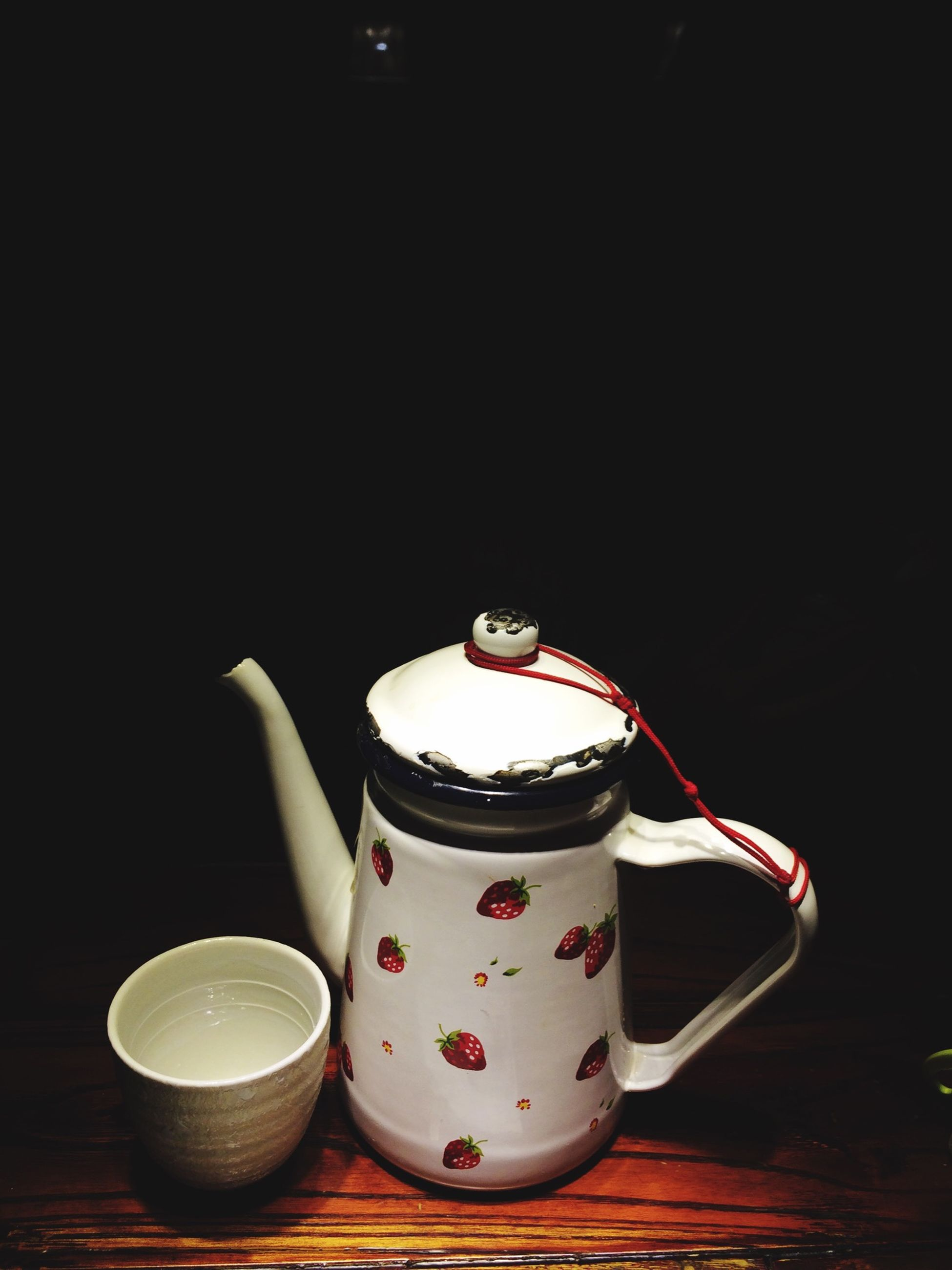 indoors, table, still life, candle, illuminated, food and drink, close-up, flame, lit, coffee cup, black background, drink, home interior, no people, burning, cup, wood - material, red, heat - temperature, dark