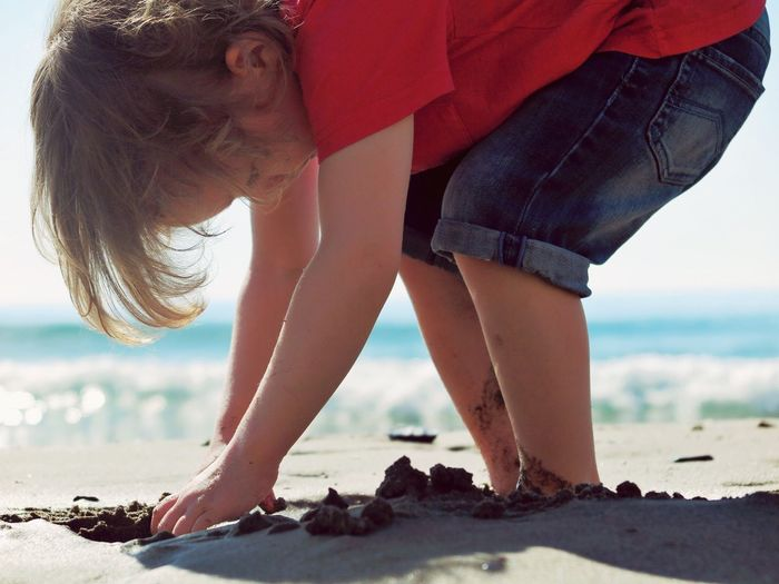 Side View Of Little Boy Playing On Wet Shore During Sunny Day