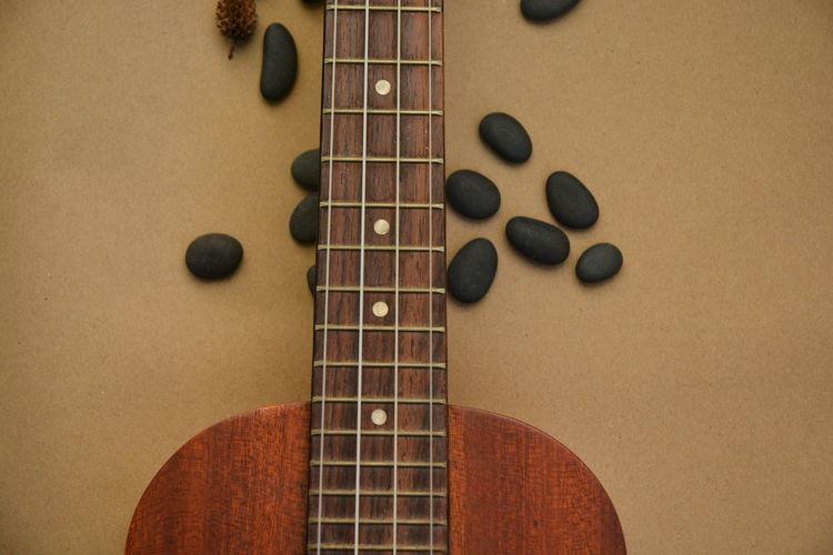 Close-up of guitar and pebbles on table