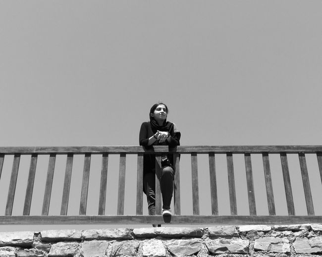 Portrait of young woman standing on railing against clear sky