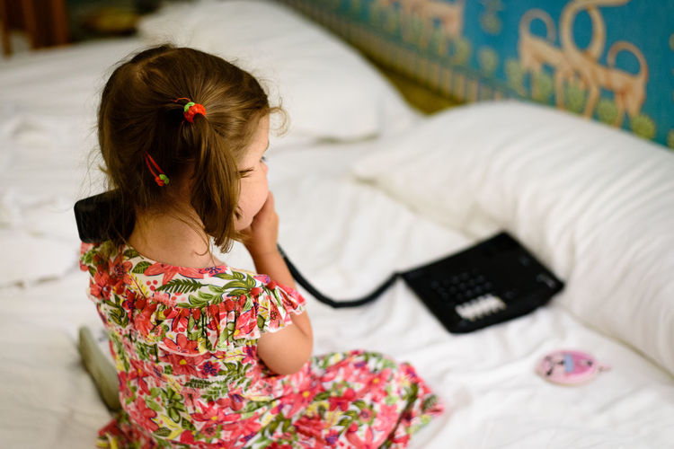 Little child in a flower dress playing with a telephone Children Happy Bed Bedroom Child Childhood Childhood Memories First Eyeem Photo Floral Pattern Furniture Girl Girls Indoors  Innocence Play Playing Real People Relaxation Telephone
