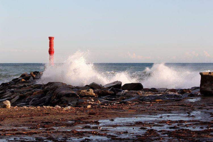 Waves breaking against sea against clear sky