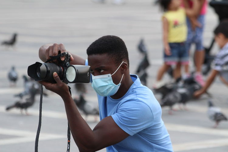 Portrait of young man photographing on street