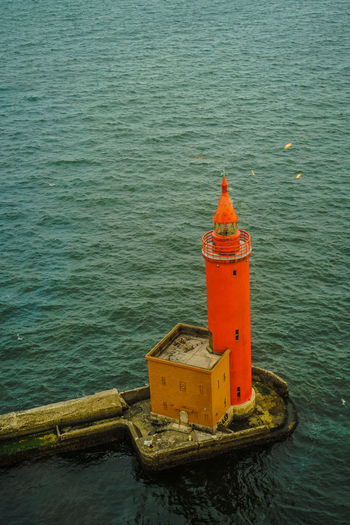 High angle view of red lighthouse by sea