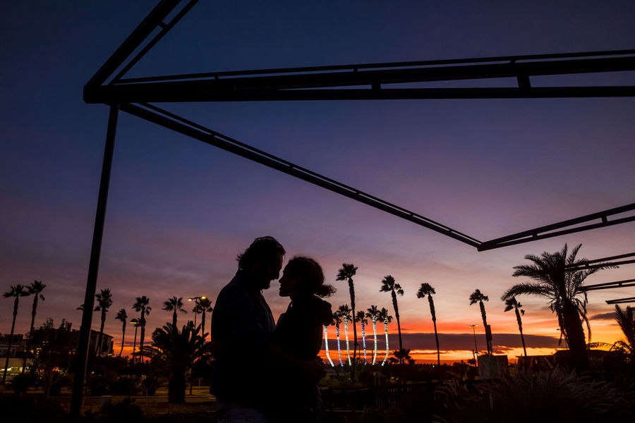 romantic couple in love outdoor in sunset between palm trees Bonding Built Structure Clear Sky Couple In Love Day Lifestyles Love Nature Outdoors Palm Tree People Real People Silhouette Sky Suggestive Place Sunset Togetherness Tree Two People