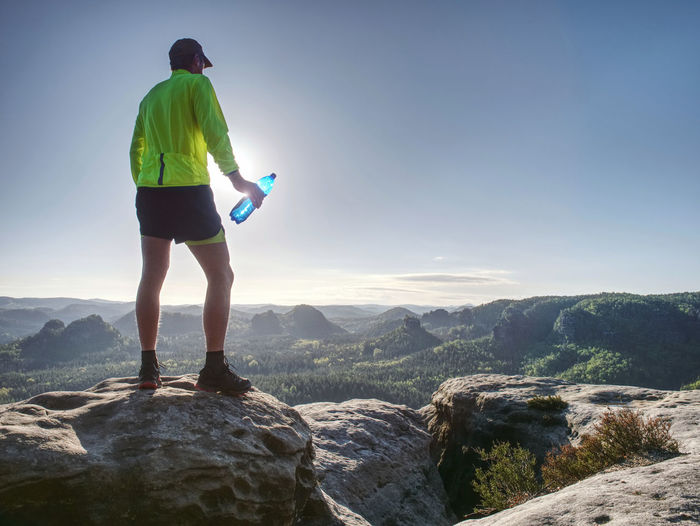 Runner in yellow green shinning jacket and black shorts jumping on rock. man athlete while jumping