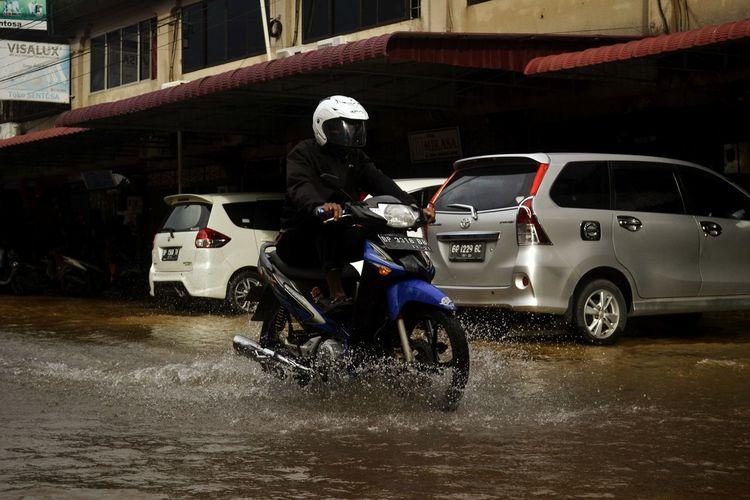 Man riding motorcycle on street during rainy season