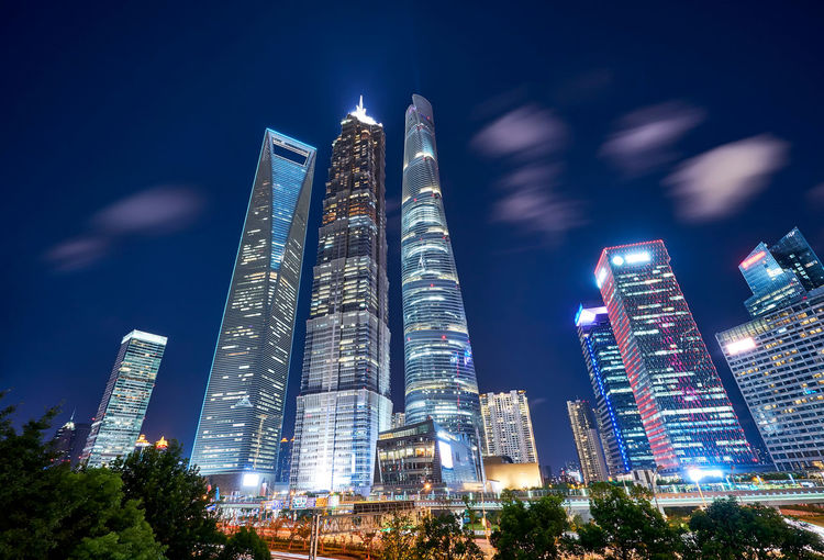 Low angle view of illuminated skyscrapers against sky at night