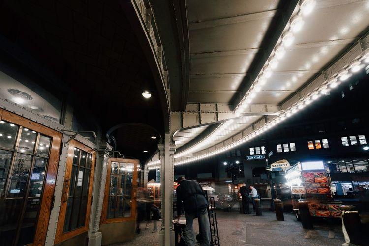 People walking in illuminated tunnel