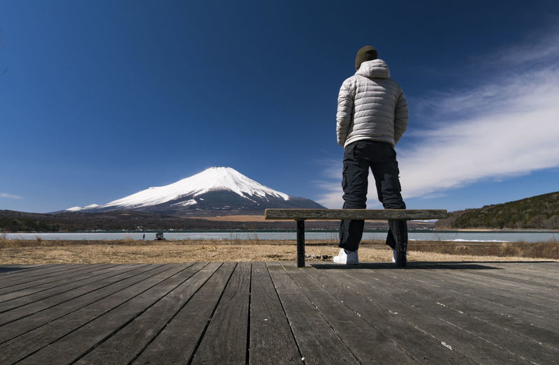 Rear View Of Man On Boardwalk Against Snowcapped Mountain