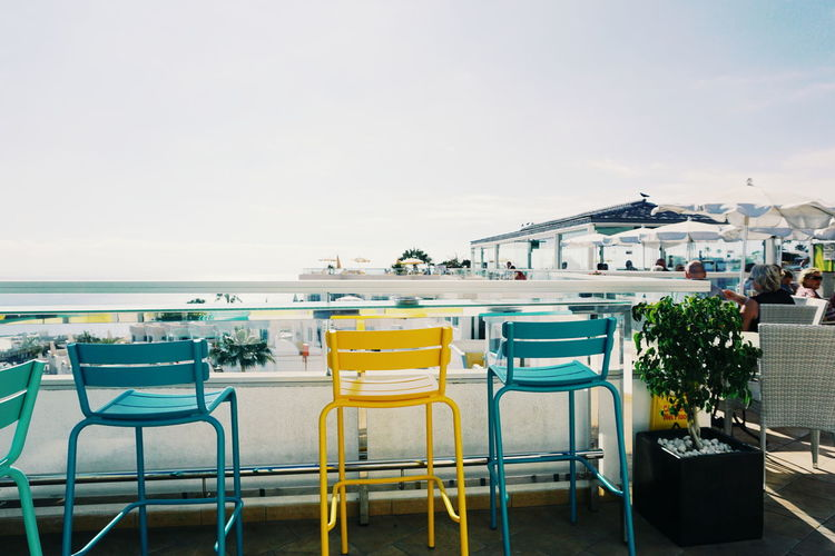 Empty chairs and tables against clear sky