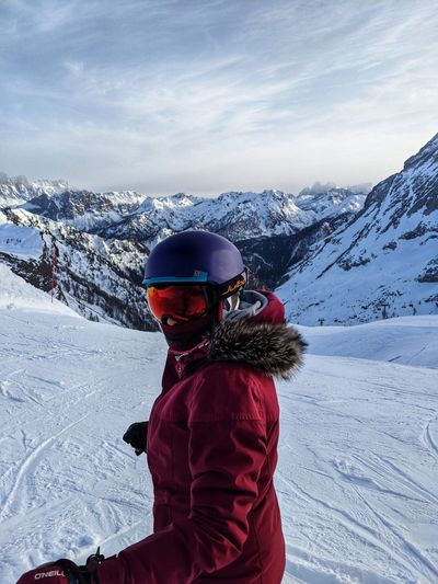 Rear view of girl on snow covered mountain against sky