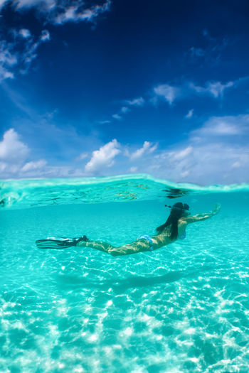 Woman snorkeling in tropical waters, half and half view Maldives Snorkeling Travel Tropics Vacations Woman Activity Bikini Blue Cloud - Sky Leisure Activity Lifestyles Model Nature Scenics Sea Sky Summer Swimming Tropical Turquoise UnderSea Underwater Vacations Water