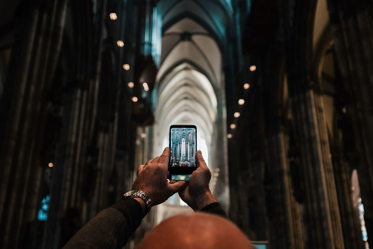 Cropped image of man photographing church with mobile phone