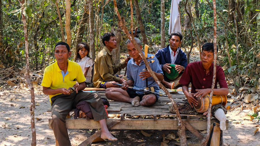 Cambodian song and Cambodoan people Sitting Tree Togetherness Drinking Day Casual Clothing Enjoyment Outdoors Happiness Adult Talking Drink People Friendship Young Adult Young Men Men Smiling Full Length Vacations People And Places Local Music Musical Instrument Musician