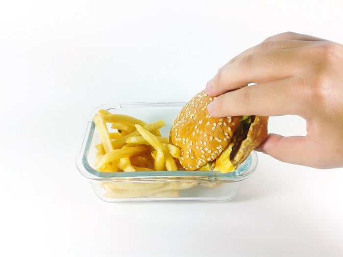 Cropped Hand Of Person Holding Hamburger In Container Against White Background