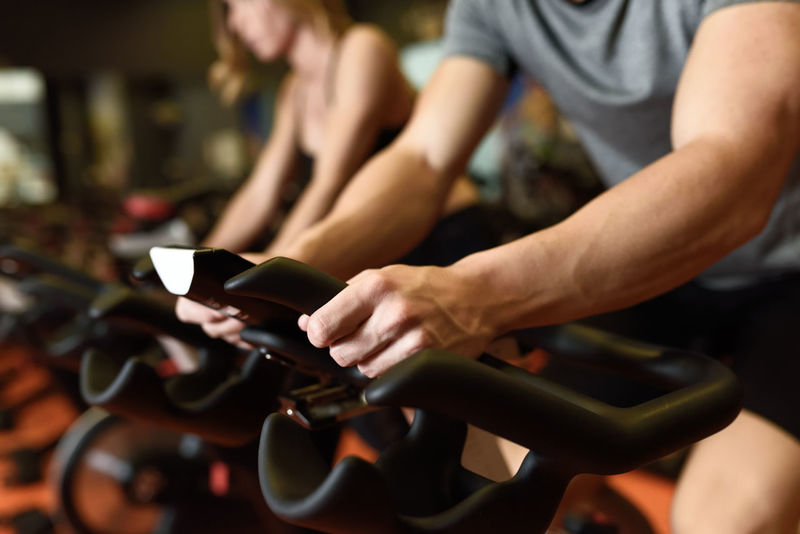 Close-up of hands of a man biking in the gym, exercising legs doing cardio workout cycling bikes. Couple in a spinning class wearing sportswear. Cyclo Exercise Exercising Cardio Cardio Exercise Close-up Cyclo Indoor Day Gym Healthy Lifestyle Human Hand Indoors  Indoors  Leisure Activity Lifestyles Men Midsection People Real People Sitting Spinning Two People Young Adult