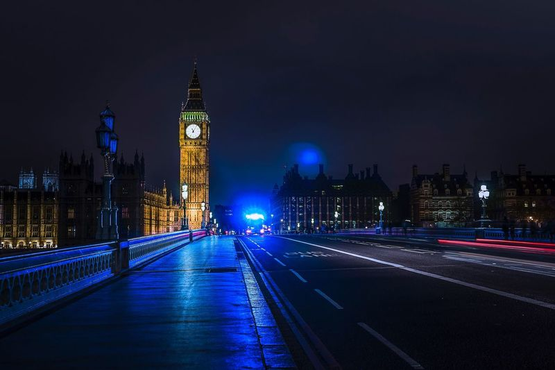 Light trails on westminster bridge by illuminated big ben against sky at night