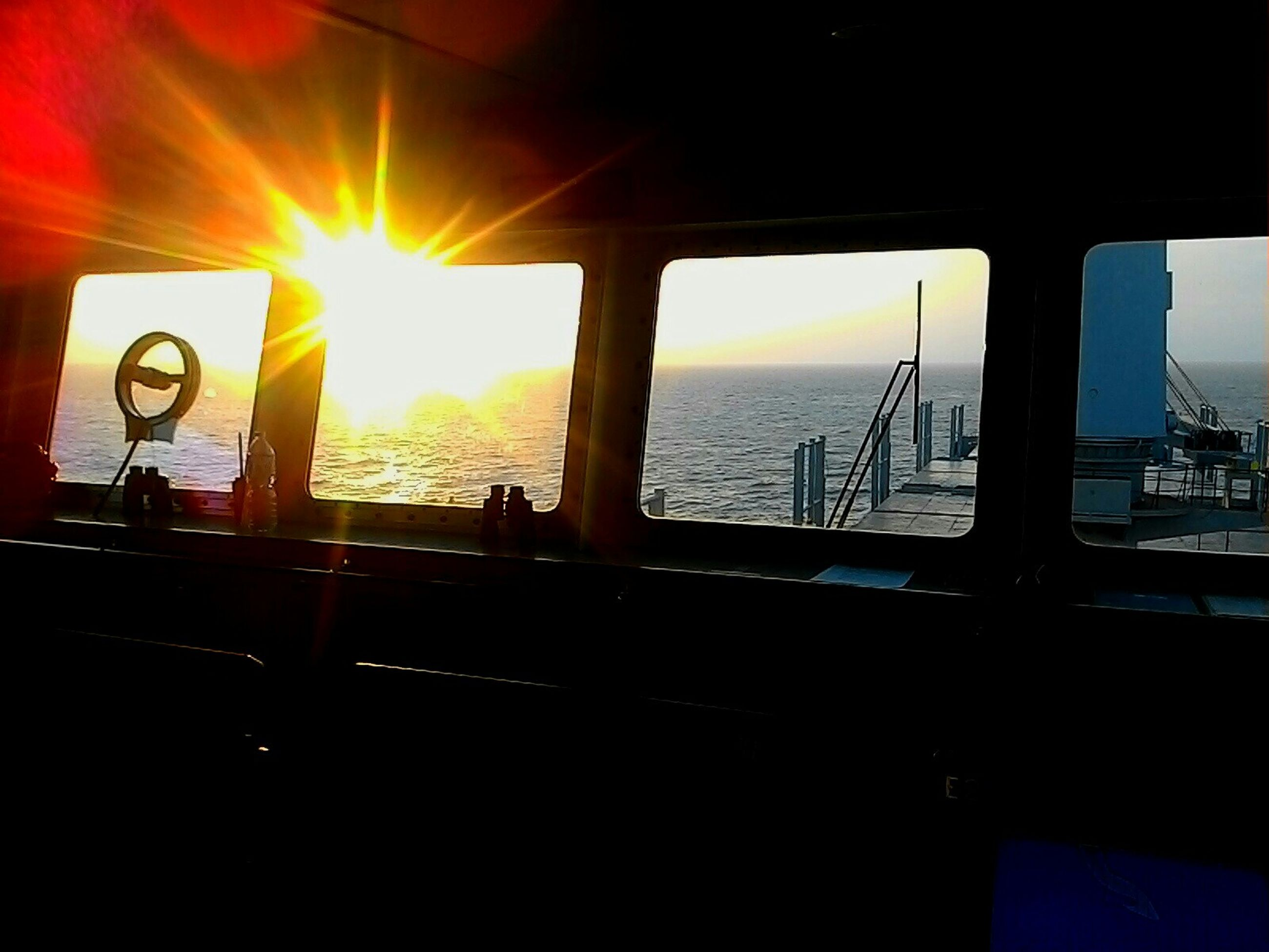 sea, indoors, sun, window, horizon over water, built structure, sunlight, sunset, architecture, sky, glass - material, water, transportation, railing, sunbeam, transparent, reflection, no people, travel, nature