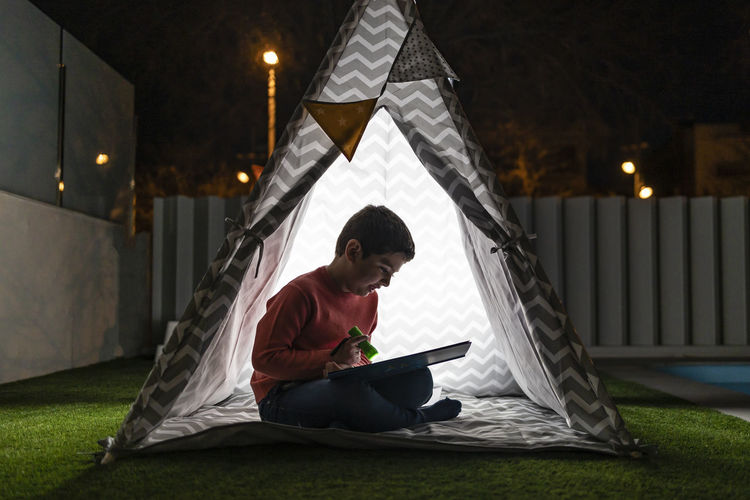 Little kid reading a book on a indian tent at night