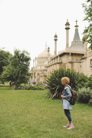 Architecture Blonde Brighton Built Structure Casual Clothing Curly Hair Day Full Length Girl Grass Grassy Green Color Growth Lawn Leisure Activity Lifestyles Outdoors Plant Royal Pavilion Royal Pavilion Gardens Sky Tourism Travel Destinations Tree