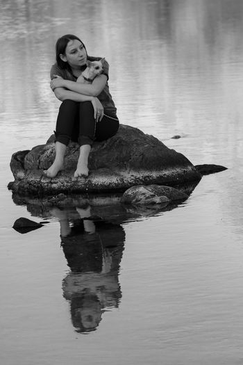 Full length of woman sitting with dog on rock in lake